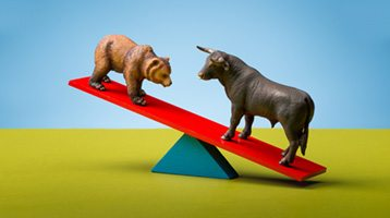 figurines of bear and bull on a seesaw
